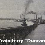 "Actual photo of the train ferry ""Duncan"" at Helena and a steamboat in the background headed up river out of Helena."